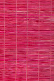 Red bamboo mat, wooden background Royalty Free Stock Photography