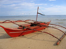 Red banca outrigger fishing boat philippines. Small red Banca traditional outrigger fishing boat on the beach negros island in the visayas the philippines stock image