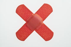 Red band-aids in the shape of an X Stock Image