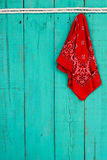 Red bandana hanging by rope border on antique blue wooden background Royalty Free Stock Image