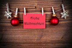 Red Banner with Frohe Weihnachten. Red Banner with the German Words Frohe Weihnachten which means Merry Christmas Hanging on a Line, German Christmas Greetings royalty free stock photography