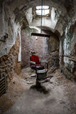 Red barber chair in a jail cell. A creepy old barber chair in Eastern State Penitentiary, Philadelphia Royalty Free Stock Photos