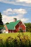Red Barn. Old Red barn with a green roof on a summer day with puffy white clouds located in Maine stock image