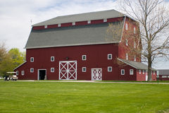 Red Barn. A photo of a red barn with white trim. In the foreground is green grass Stock Image