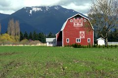 Red Barn. Viewed in spring with a cut corn field in the foreground Royalty Free Stock Photos