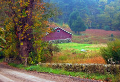 Red Barn. View of old red barn and dirt road in early autumn royalty free stock image