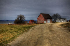 Red Barn Along the Dirt Road. Driving along the dirt road, we see a red barn with a view of the ocean Royalty Free Stock Image