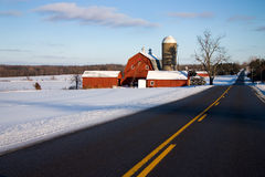 Red Barn Along Road in Winter. A red barn with snow along side a road in winter Stock Images