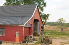 Red barn in barnyard. A large red barn and tractor in a working farm barnyard Royalty Free Stock Images