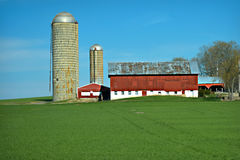 Red Barn. A beautiful red barn landscape with two silos, green spring wheat and blue skies Stock Photography