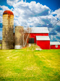 Red Barn, Blue skies and the green, green grass of home. An abstract, instagram - like, heavy colour and contrast image of a beautiful red barn with blue skies Stock Images