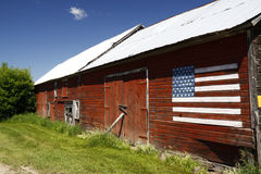 Red Barn, Blue Sky, American Flag. A red wooden barn with a white tin roof and painted American flag in the Adirondacks in rural upstate New York on a blue sky stock photography