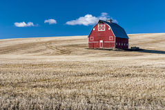 Red barn blue sky and wheat stuble field Royalty Free Stock Photos