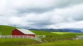 Red barn building and white fencing offers contrasting image Royalty Free Stock Photography