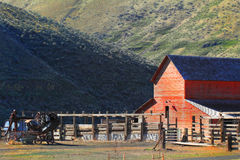 Red Barn and Corrals. The front of a large red working country barn with corrals sits at the base of some steep grassy hills Stock Photos