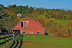 Red Barn in the Countryside. A red flattened hip roof barn with an open hay loft door is surrounded by the colorful autumn trees Stock Images