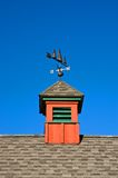 Red barn Cupola. A view of a red cupola and weather vane on top of a barn on a sunny, cloudless summer day. Vertical perspective stock photo
