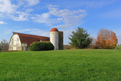 Red Barn and Dairy Silo on Green Meadow. Fall Landscape with red barn, silos, green meadow, and colorful trees on blue sky Stock Image