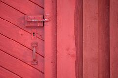 Red barn door with handle and key hole and deadbolt lock. Closeup Royalty Free Stock Images