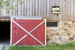 Red Barn Door. Partially open red barn door in a weathered barn.  Traditional white framing, weathered wood, field stone, texture and nostalgia Stock Photography