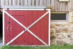 Red Barn Door. Partially open red barn door in a weathered barn.  Traditional white framing, weathered wood, field stone, texture and nostalgia Royalty Free Stock Photos