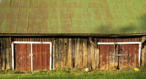 Red barn doors on an old shed with a green roof Royalty Free Stock Photos