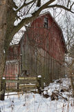 Red Barn. Faded and weather-worn red barn framed by the snow of Western New York royalty free stock photo