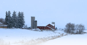 Red barn and falling snow Stock Photos