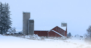 Red barn with falling snow Stock Images