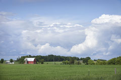 Red barn and field below dramatic cloudscape Royalty Free Stock Photo