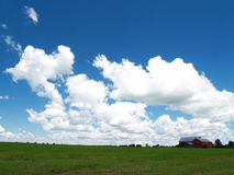 Red Barn, Fluffy clouds2. A red barn on a beautiful summer day Stock Photos