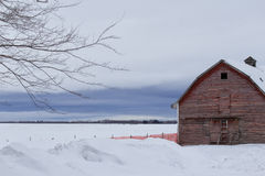 Red barn front in winter. Weathered front of a barn under cloudy sky in winter Royalty Free Stock Images