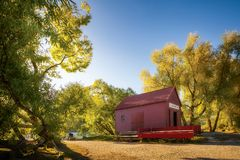 The Red Barn at Glenorchy Wharf, New Zealand. Small barn at Glenorchy Wharf close to sunset with the trees on the lake shore glowing at golden hour - Otago Stock Photo