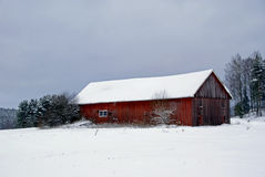 Red Barn on a Grey Winter Afternoon. An old red barn by the field on a grey January afternoon. Photographed in Salo, Finland in January 2011 Royalty Free Stock Image