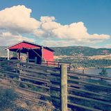 Red barn on hillside with lake, hills and sky background Stock Images