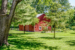 Red Barn in Large Yard Surrounded by Trees Stock Photos
