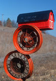 Red barn mailbox on tire rims Royalty Free Stock Photography