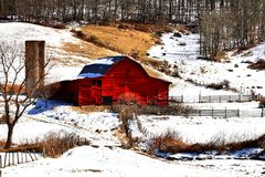 Red Barn. In the mountains of North Carolina red barns dot the landscape. Beautiful red barn surrounded by a lite snowfall Royalty Free Stock Image