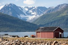Red barn on Norway fjord shore. And mountain view background Stock Image