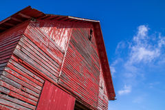 The red barn. The old red barn side and roof with brilliant blue sky background Stock Photos