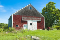 Red barn in Maine. Red shingled barn and old red tractor at summertime in Maine Royalty Free Stock Photos