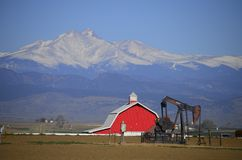 Red Barn Pump Jack Oil well and Longs Peak Royalty Free Stock Image