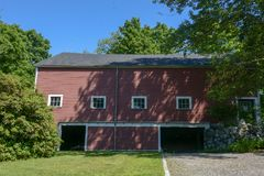 Red Barn set against a deep blue sky in Groton MA on a sunny summer day. Three story barn with 4 windows and 2 barn door entrances. White trimmed 6 pane windows Stock Photo