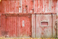Red Barn Side. The side of a red barn showing the sliding door and faded red paint Royalty Free Stock Image