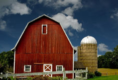 Red barn and silo. Vintage red barn and silo with a white fence against a blue sky Royalty Free Stock Photography