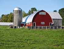 Red Barn with silo. The setting sun highlights a red barn and silo at a farm Stock Photo