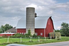 Red barn and silo without cap. A red barn with a white roof and a topless silo against a cloudy blue sky Royalty Free Stock Image