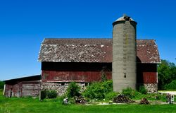Red Barn & Silo In Walworth County. This is a Summer picture of an oldl multiple-purpose red barn and silo against a blue sky located in Walworth County stock images