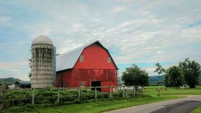 Red Barn With Silo in Wisconsin. A red barn with a silo and a wooden fence in front located in the countryside of Wisconsin royalty free stock photos