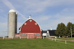 Red barn with silo& x27;s and white fence Stock Image